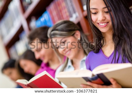 Group of students at the library enjoying reading - stock photo