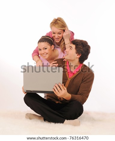 Group of students having fun with laptop on white background. - stock photo