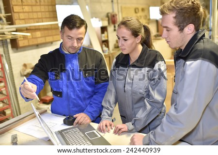 Group of students listening to teacher in workshop - stock photo