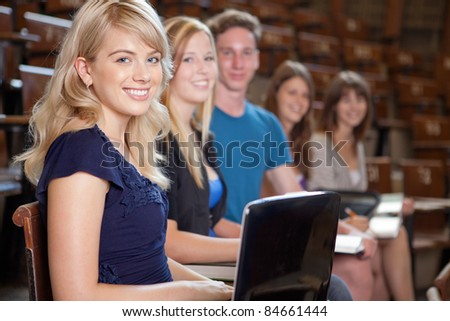 Group of students looking at camera in a university lecture hall - stock photo