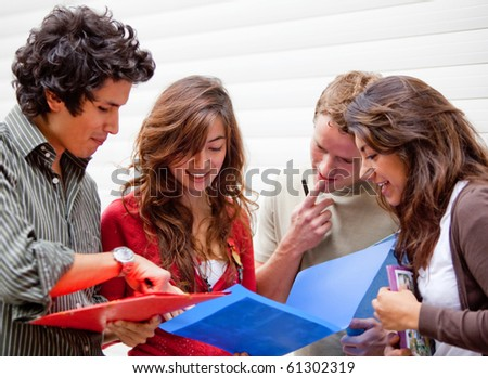 Group of students looking at notebooks and debating - stock photo
