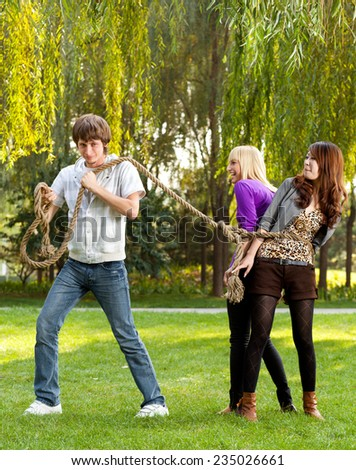 Group of students Man dragging two women Tug-of-war Outdoors shoot - stock photo