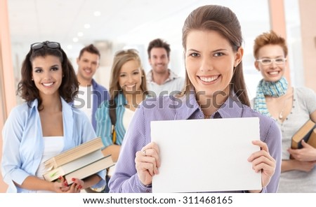 Group of students on school corridor. Girl in front holding blank sheet, paste your text there. - stock photo