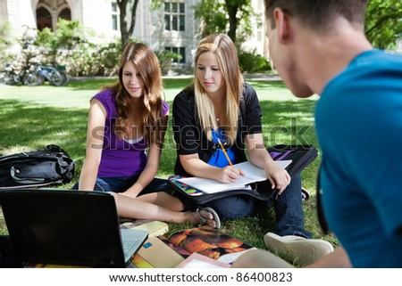 Group of students on the campus grass with laptop and books - stock photo