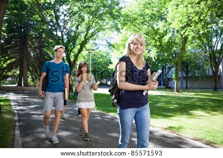 Group of students on their way to class walking through campus - stock photo