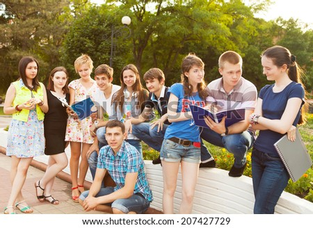 Group of students or teenagers with notebooks outdoors in summer evening