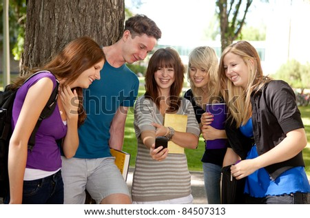 Group of students outdoors looking at a humorous image on a cell phone - stock photo