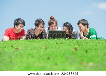 Group of students outdoors lying on grass and looking computer - stock photo