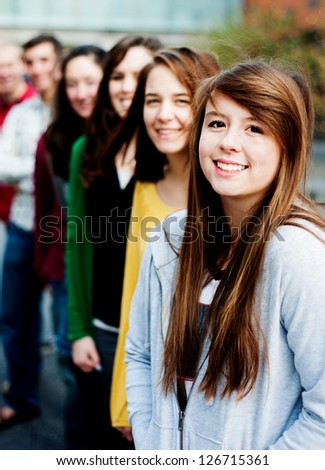 Group of students outside smiling in a line together - stock photo