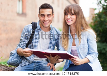 Group of students reading a book - stock photo