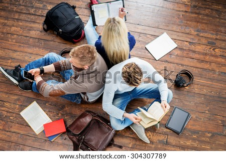 Group of students reading books, writing in notebooks and using a smartphone leaning on each other on wooden floor.  - stock photo