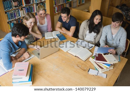 Group of students sitting at a table in a library while learning and using tablet and laptop
