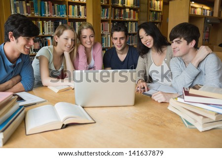 Group of students sitting at a table in a library while learning and using the laptop