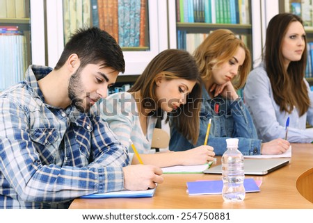 Group of students sitting at table in library - stock photo