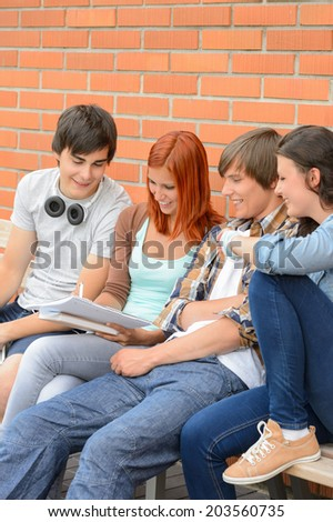 Group of students sitting bench outside college writing notes brainstorming - stock photo