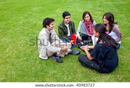Group of students sitting in a circle outdoors - stock photo