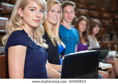 Group of students sitting in a row with laptop and book at seminar hall - stock photo