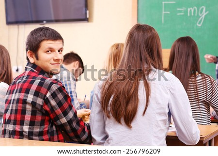 Group of students sitting in classroom and  listening teacher - stock photo