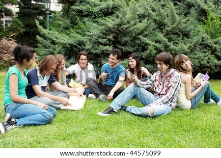 Group of students sitting in park on a grass - stock photo