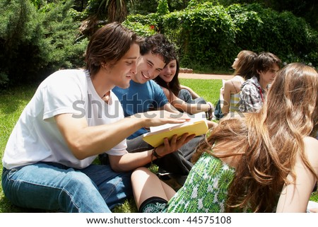 Group of students sitting in park on a grass