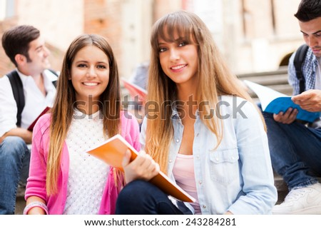 Group of students sitting on a staircase. Selective focus, shallow depth of field - stock photo