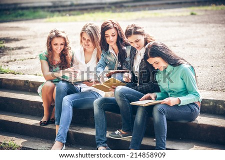 Group of students sitting with a books on street - stock photo