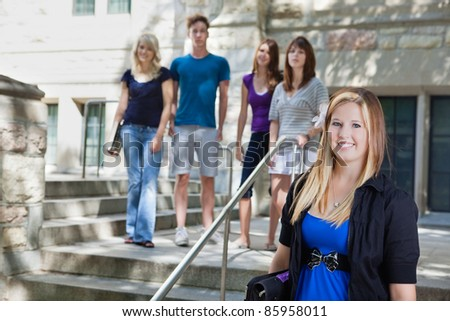 Group of students standing at college building - stock photo