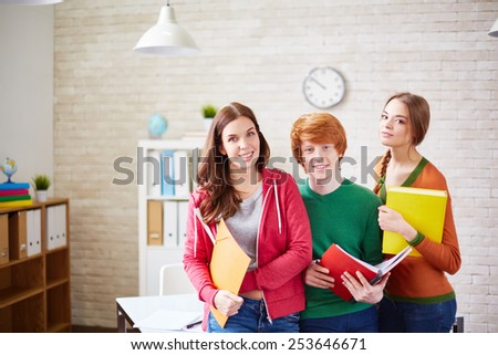 Group of students standing by desk in classroom