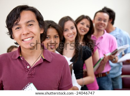 Group of students standing in a row at a classroom - stock photo