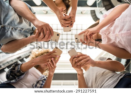 Group of students standing in circle and using phones. - stock photo