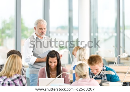 Group of students study in classroom at highschool with professor - stock photo