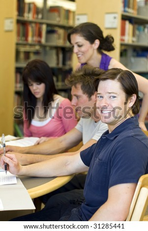 Group of students studying at the library - stock photo