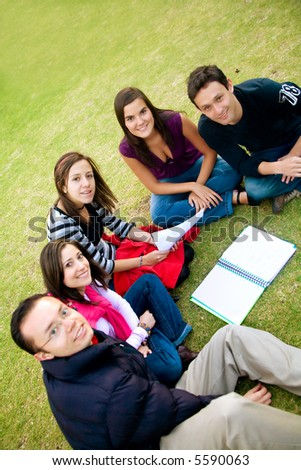group of students studying outdoors in a college park - stock photo