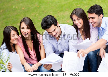 Group of students studying outdoors looking very happy - stock photo