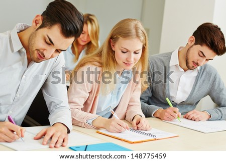 Group of students studying together in university class - stock photo