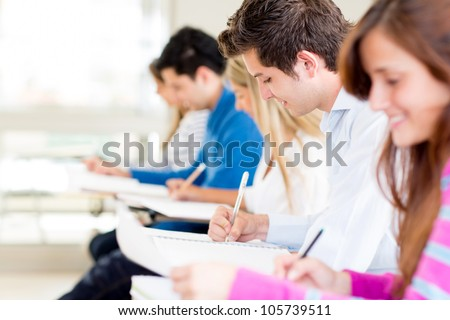 Group of students taking a exam at the university - stock photo