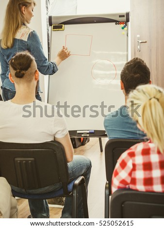 Group of students taking a part in maths lesson while sitting in lecture hall. Young teacher teaching mathematics, writing math formulas on the board
