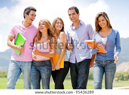 Group of students talking a walk outdoors and smiling - stock photo