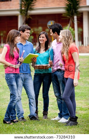 Group of students talking and holding notebooks outdoors - stock photo