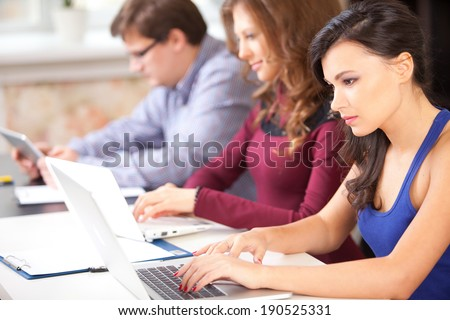 Group of students using a laptop computer - stock photo