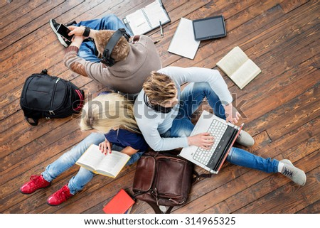 Group of students using smartphones, laptops and reading books in headphones listening to the music and leaning on each other on wooden floor having notebooks and bags around them.   - stock photo