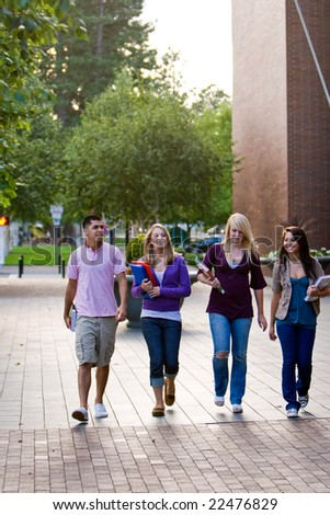 Group of students walking, talking, smiling, and carrying books. Vertically framed photo. - stock photo