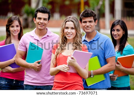 Group of students with a notebook outdoors - stock photo