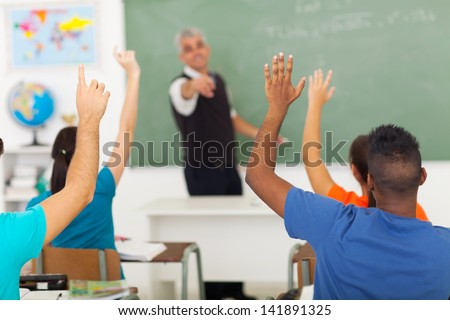 group of students with hands up in classroom during a lesson - stock photo