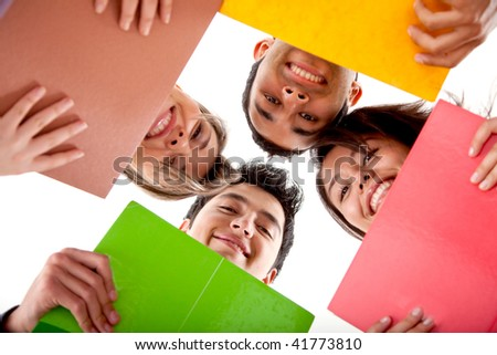 Group of students with notebooks and heads together isolated