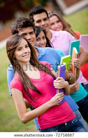 Group of students with notebooks outdoors and smiling - stock photo