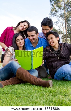 Group of students with notebooks studying outdoors