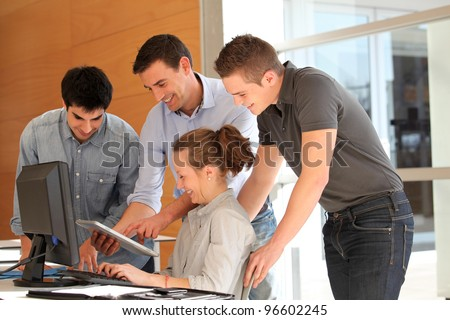 Group of students with teacher working on computer - stock photo