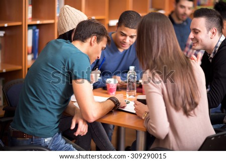 Group of students working their task in team in library - stock photo