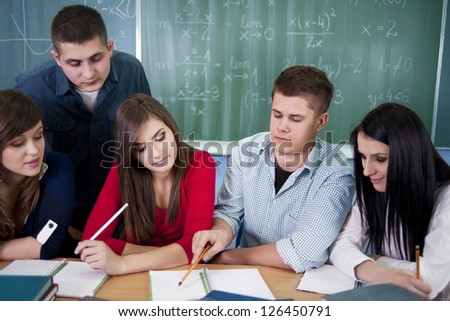 Group of students working together in the classroom - stock photo